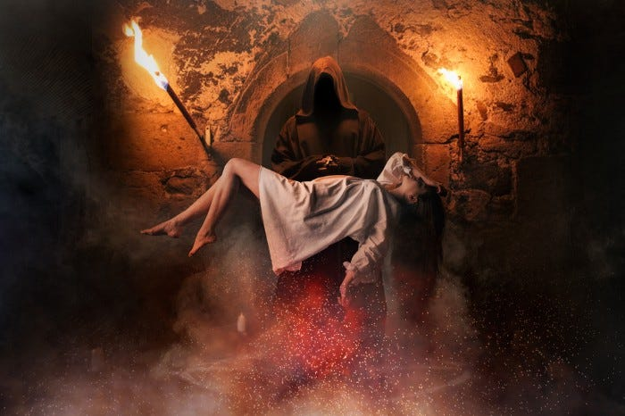 Hooded figure folding a unconscious woman in a crypt illuminated by torches