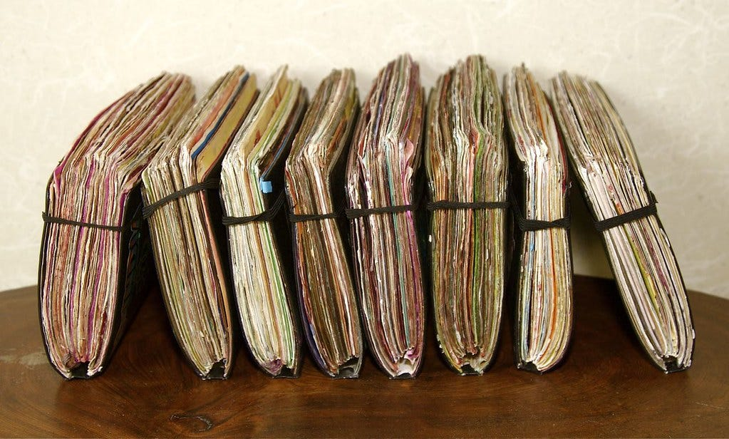 """A row of closed, handmade journals. """"journals"""" by gbSk is licensed under CC BY 2.0"""