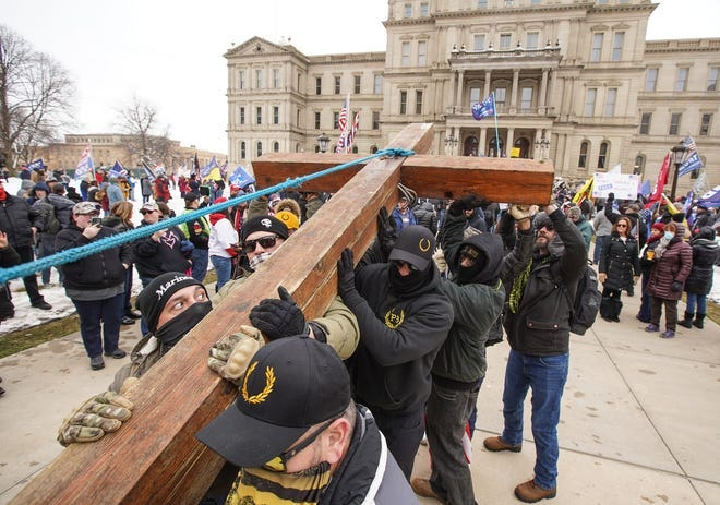 Members of the Proud Boys and others help James Chapman of Belleville raise a large red cedar cross he brought as hundreds of Trump supporters gather outside of Michigan's State Capitol building in Lansing on Wednesday, January 6, 2021 during a rally to pray for Trump.