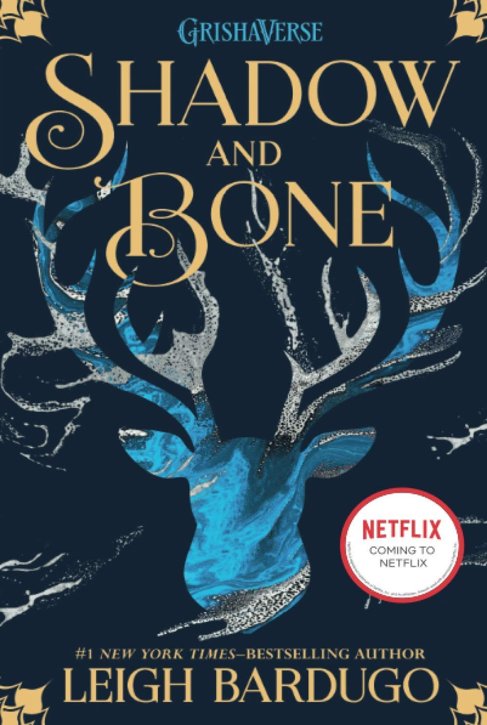 The navy blue cover of Shadow and Bone by Leigh Bardugo, depicting a light blue and gray stag and the rest of the text in gold, swirling font.