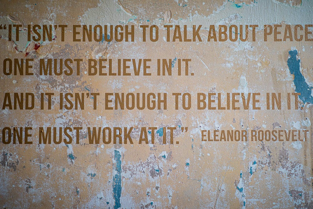 """Eleanor Roosevelt's quote on the wall at Refuge Coffee Co. """"It isn't enough to talk about peace. One must believe in it. And it isn't enough to believe in it. One must work at it.""""  Art design by  _@chase.moore ."""