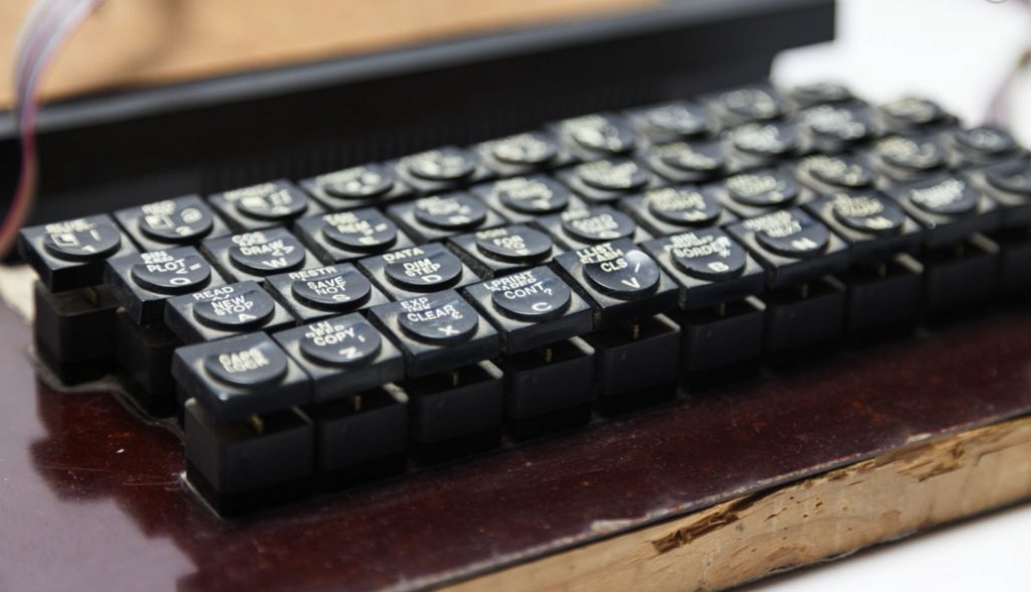 Keys from a Spectrum hand-soldered onto a varnished wooden board to make a replacement keyboard.