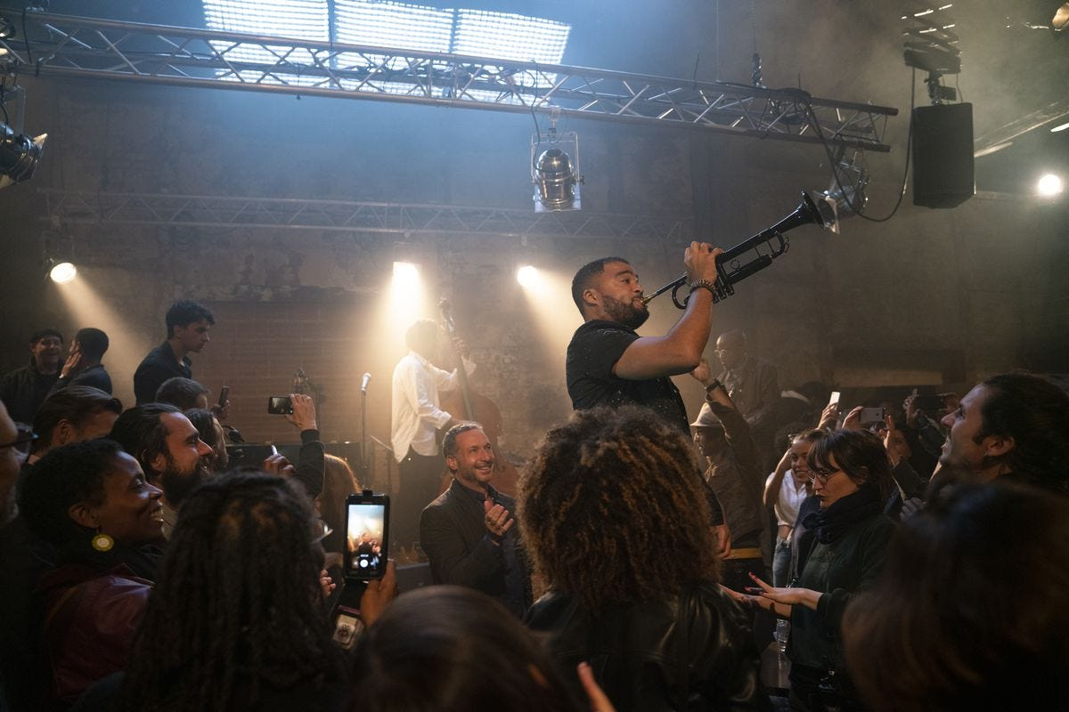 In a scene from The Eddy, an audience gathers around a performer who's standing on stage, blowing into a muted black trumpet.