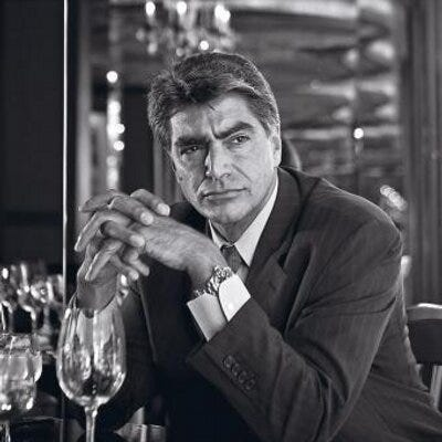 Wearing a suit, Mark Rossini leans over an empty glass at a restaurant table