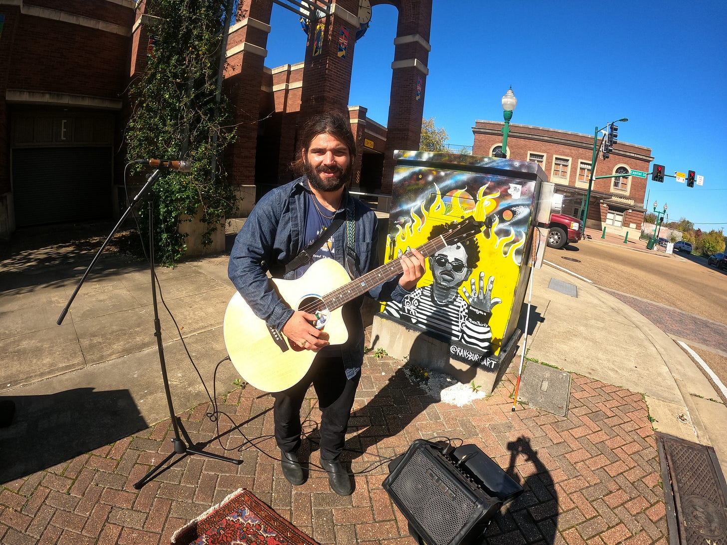 Anthony posted up on the corner getting ready to live stream to Facebook in Jackson, Mississippi a piece of art work is behind him with a guy released from jail in a yellow flame and sunglasses