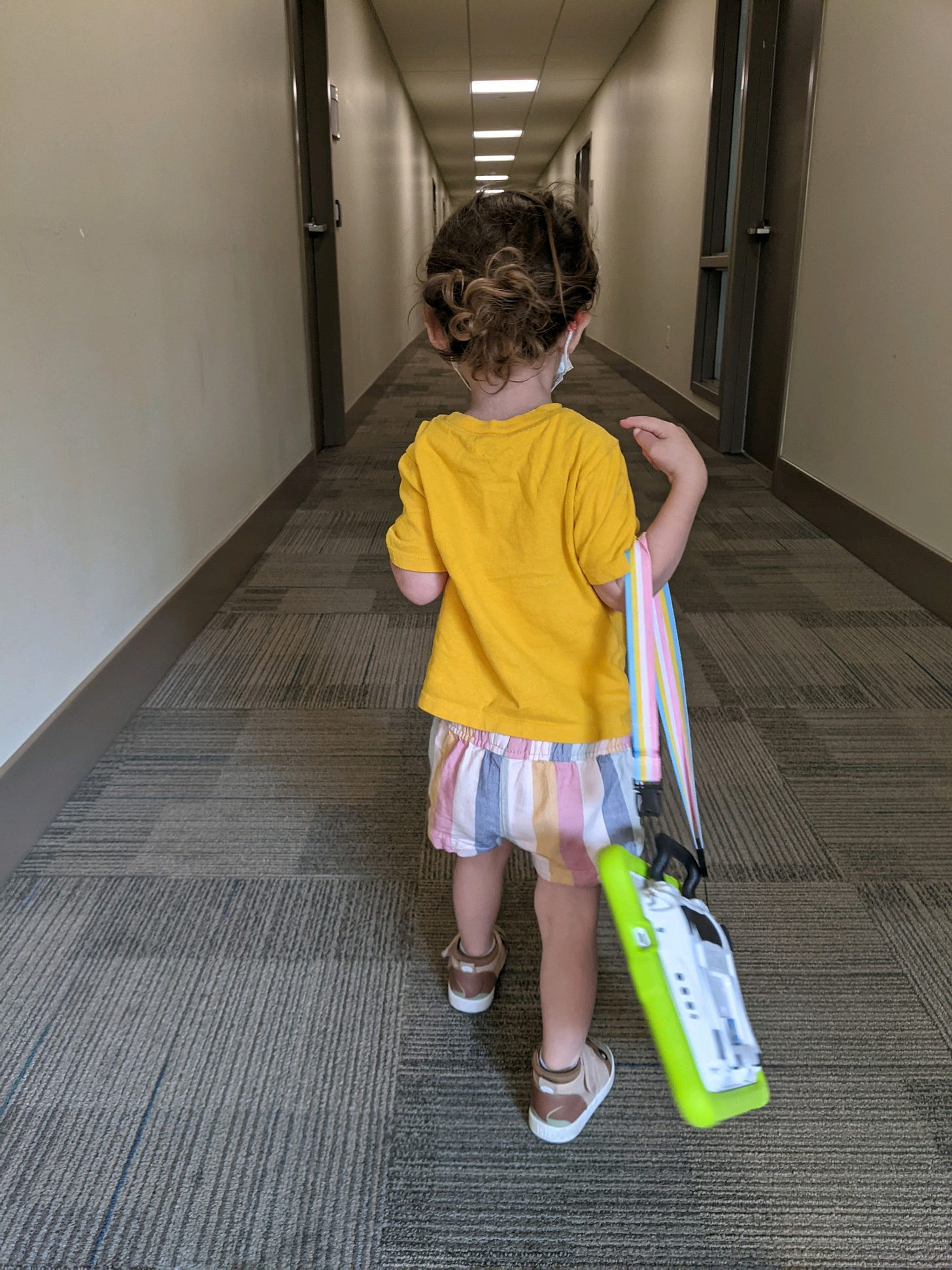 Photo of Lila walking away down a hallway holding her talker over her arm.