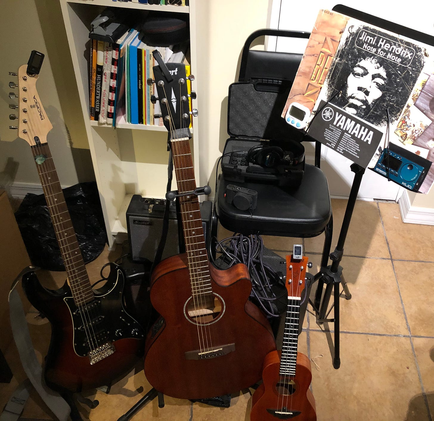 Electric guitar, acoustic guitar, ukulele, amplifier, camera, chair, music stand, and metronome. Recording device and headphones.