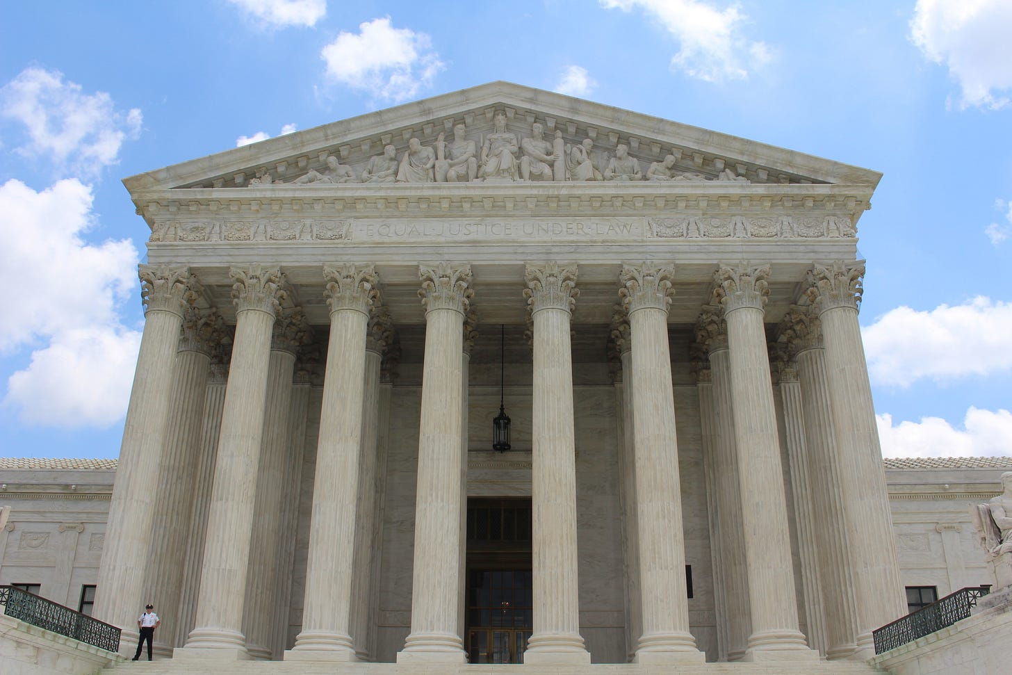 Photo of the front of the Supreme Court building taken on a sunny day with blue sky and white clouds in the background.