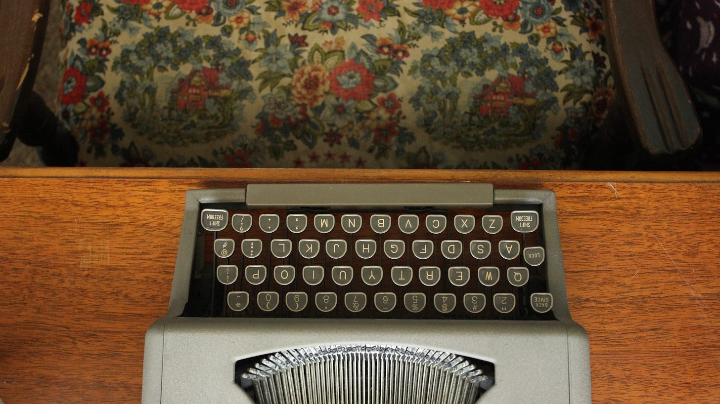 bird's eye view of a manual typewriter on a scuffed wooden desk; part of a chair with floral upholstery can be seen at the top of the image