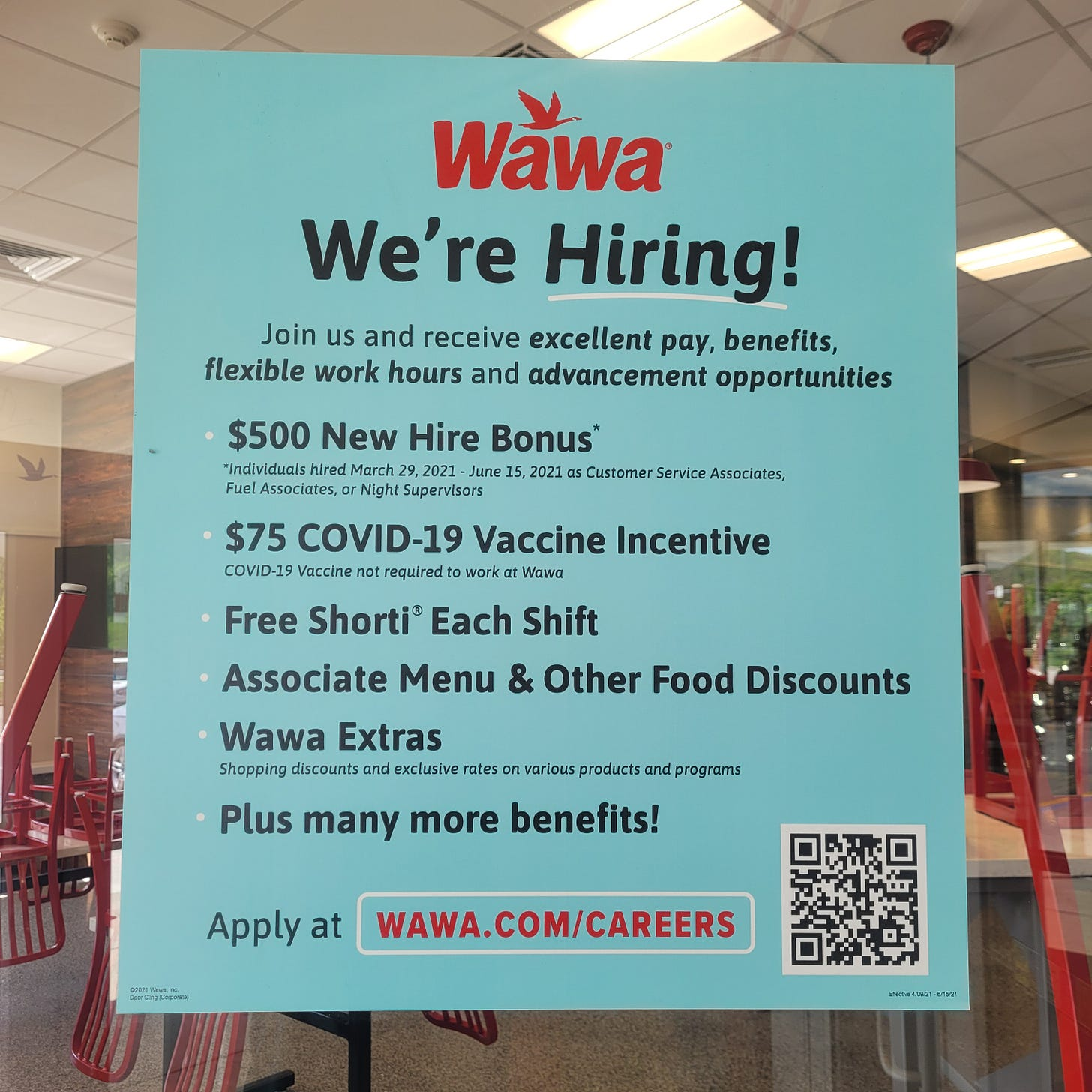 A sign at Wawa announcing the perks of working there, including a $500 hiring bonus, vaccine incentive, employee meals, discounts, and more.