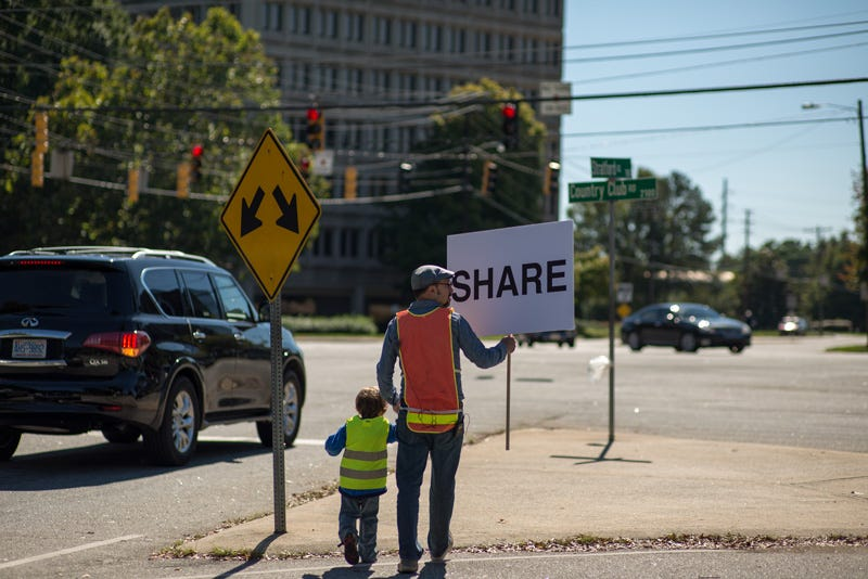 """A man and his son cross a street carrying a sign that says, """"SHARE"""""""
