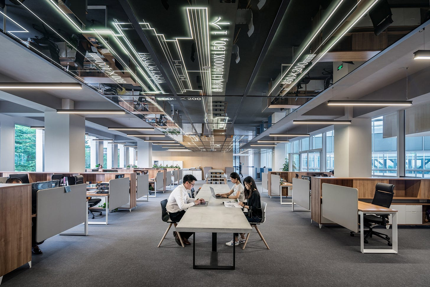 Image of workers working in an open plan office for article by Larry G. Maguire