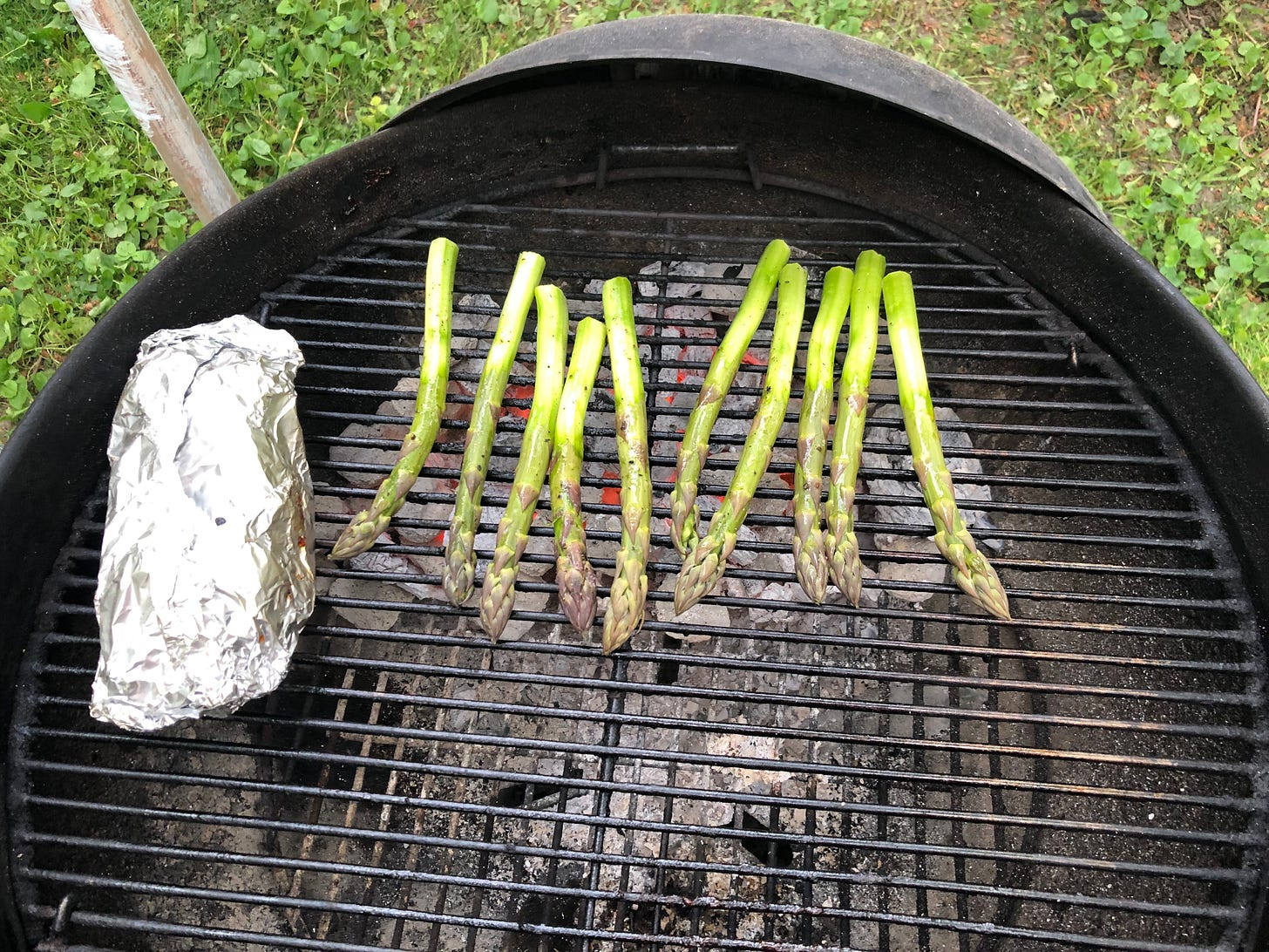 Asparagus grilling on a hot charcoal grill. Beside them on the grill is a foil packet.