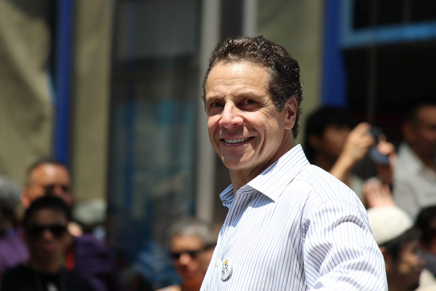 photo of Andrew Cuomo standing on a sunlit NY street