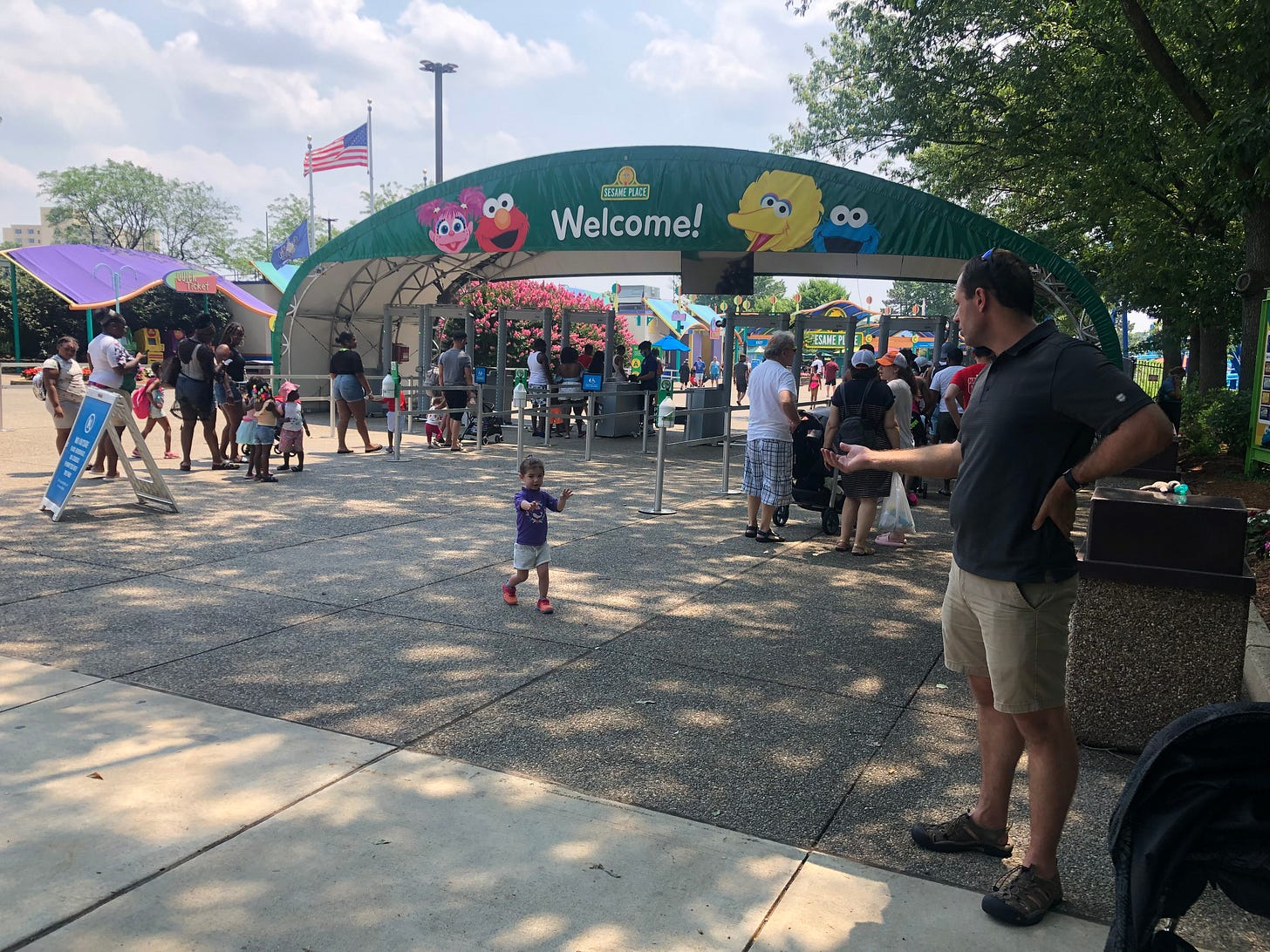 Photo of entrance of Sesame Place and Lila holding her hands out signing for Mark to join her.