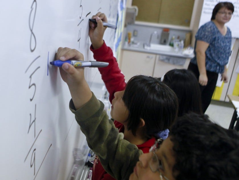 Students at Los Angeles Elementary School solve math problems at a whiteboard.