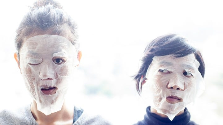 Two women wear skin-care face masks.