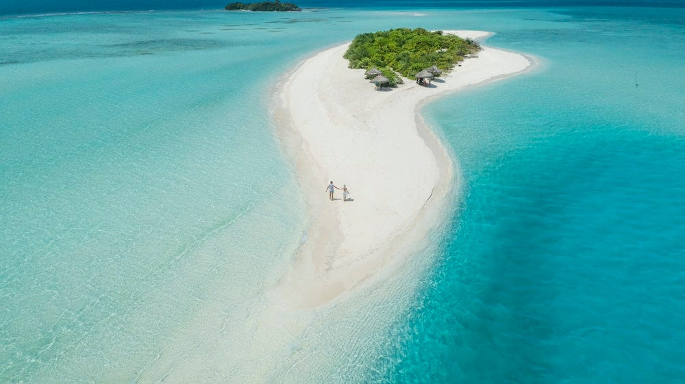 two person walking on islet during daytime