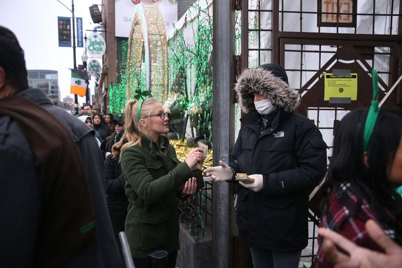 A doorman wears a mask while accepting money from patrons celebrating an early St. Patrick's Day on Clark Street in Chicago's Wrigleyville neighborhood on March 14, 2020.