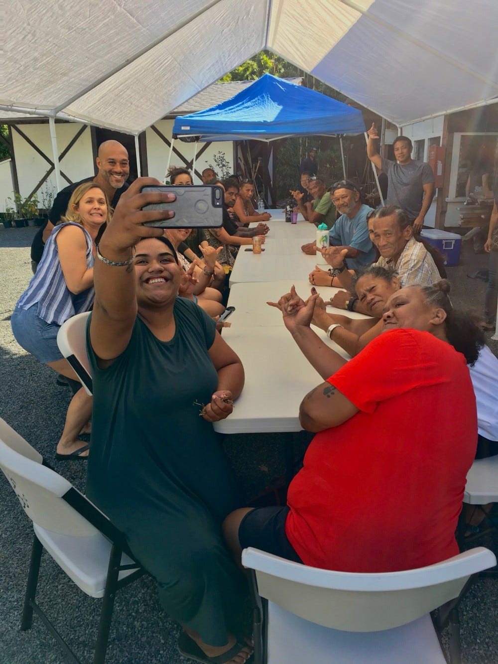 A group of people pose for a selfie around a table, throwing shakas.