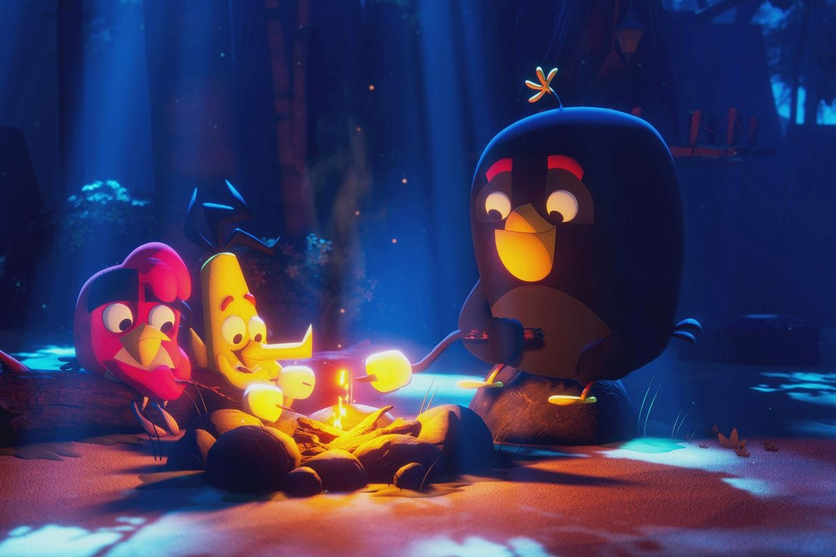Angry Birds Red, Bomb, and Chuck toast marshmallows around a campfire
