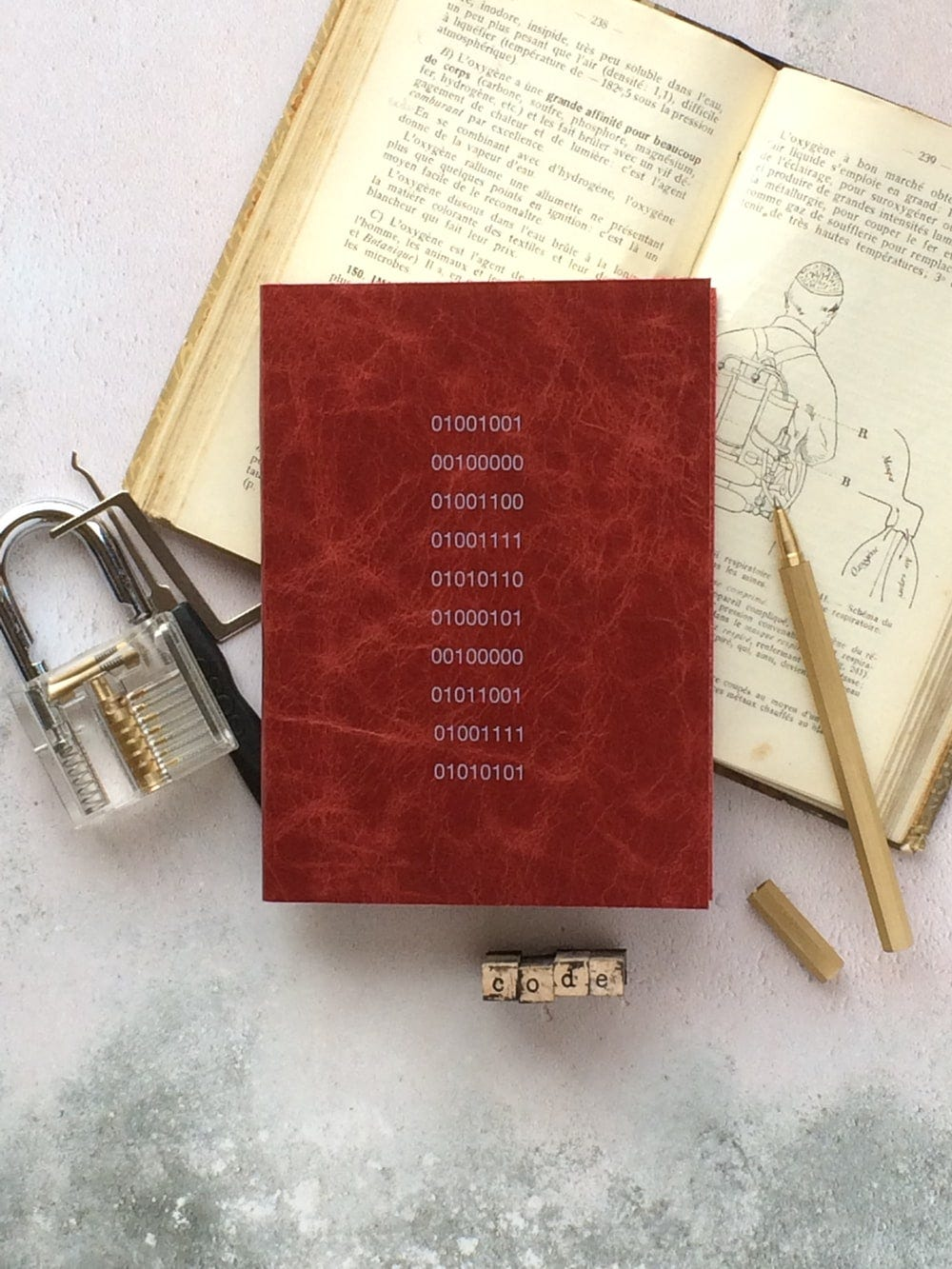 stainless steel padlock beside book and pen