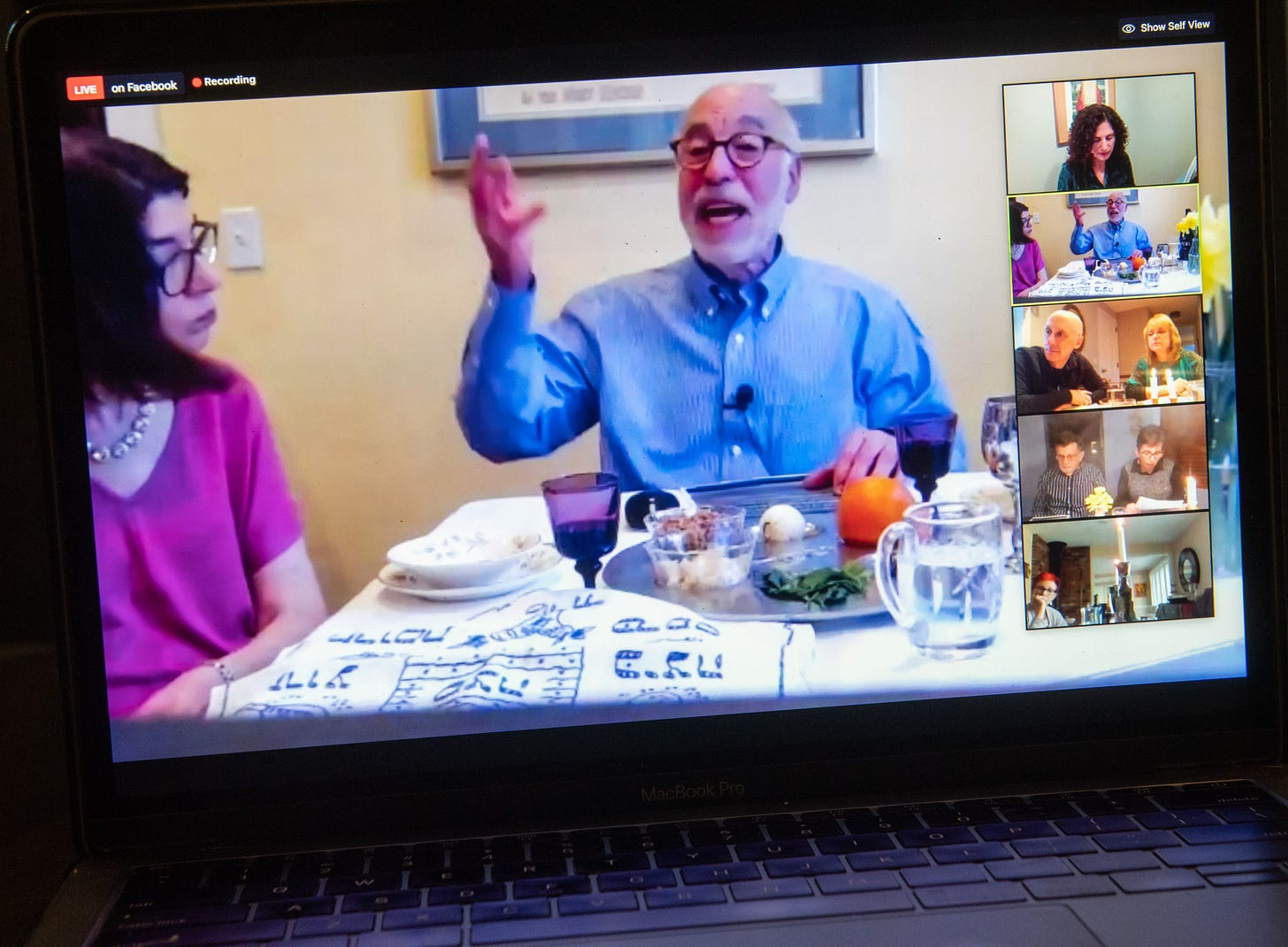 This image shows a man on a laptop screen during Seder