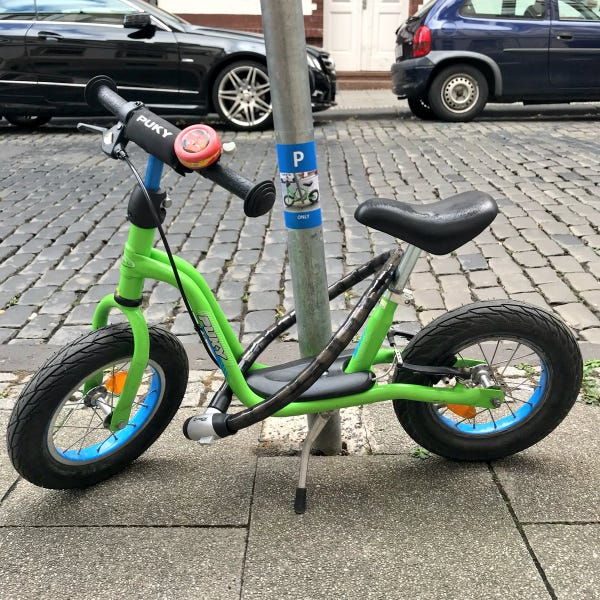 Children's bicycle chained to a lamppost.