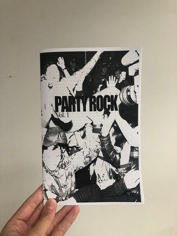 a photo of my hand holding a zine, with a black and white cover of people partying, which says PARTY ROCK Vol. 1 on it