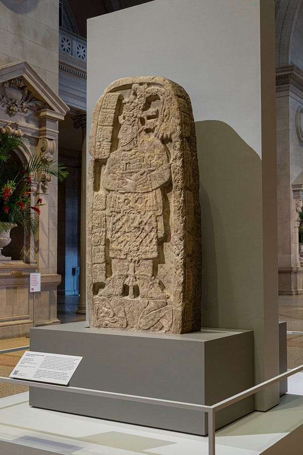 A rounded Mayan stone stela carved to represent an ancient queen. She stands in profile atop a captive who crouches below her feet. The stela stands inside The Met's Great Hall.