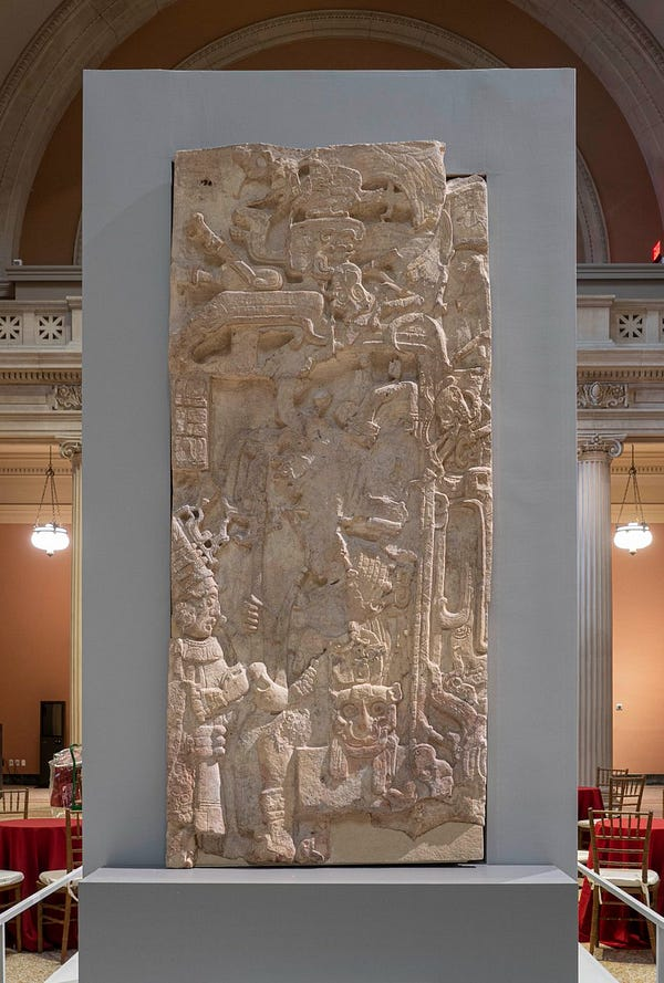 A rectangular Mayan stone stela carved to represent an ancient king. He rises to meet a visitor who enters from the left of the frame. The stela stands inside The Met's Great Hall.
