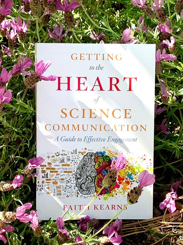 """The cover of Dr. Faith Kearns new book """"Getting to the Heart of Science Communication."""" The book is sitting in dappled sunlight in a bed of lavender flowers."""