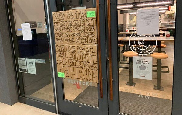 """large sign posted on door of chipotle reads: """"Sorry for the inconvenience but due to us being over worked understaffed and under appreciated we are protesting until conditions are changed"""""""