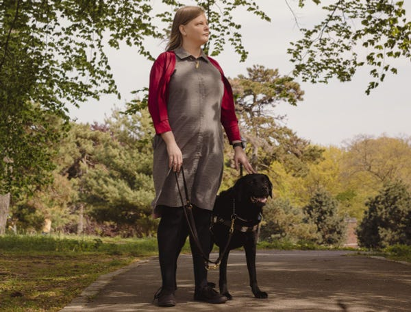 Chancey Fleet stands on a trail surrounded by trees and her loyal black dog stands next to her