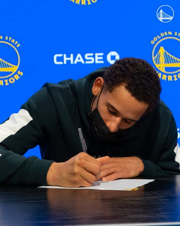 Juan Toscano-Anderson signs his contract with the Golden State Warriors in front of a Warriors backdrop.