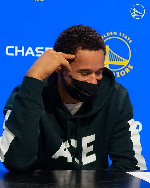 Juan Toscano-Anderson is emotional after signing his contract with the Golden State Warriors in front of a Warriors backdrop.