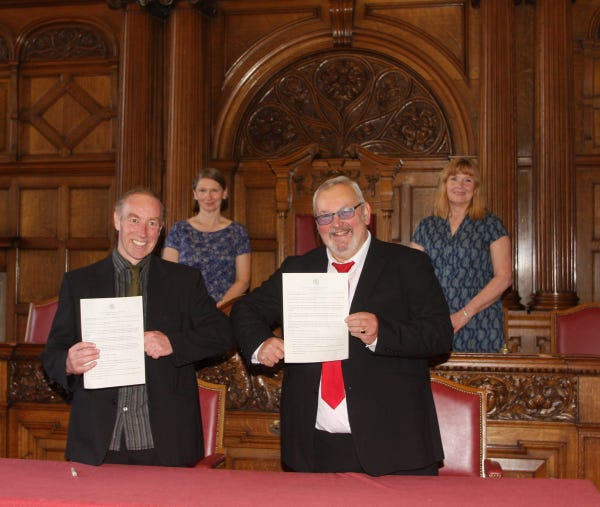 Four councillors stood holding signed agreements
