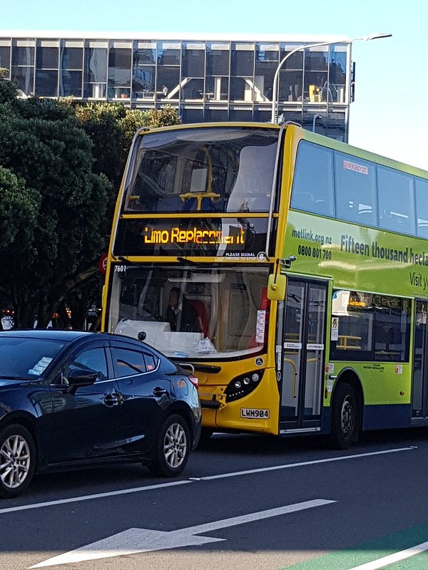 """A yellow and Green Wellington double decker bus. Stationary behind a late model car at (unseen) traffic lights, with verdant trees behind to the left, with an office building behind set against a blue winter sky. The destination display indicates """"Limo Replacement""""."""