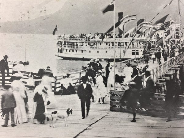 """Black and white photo of a two-deck ferry (""""City of Nanaimo"""") arriving at a dock, with a crowd of people on the dock. All are dressed in 1910s clothing (long dresses, hats, suits). The dock extends from the foreground to midground, and is lined with flags. The back ground is the shoreline of a mountain, and the atmosphere is misty and windy."""