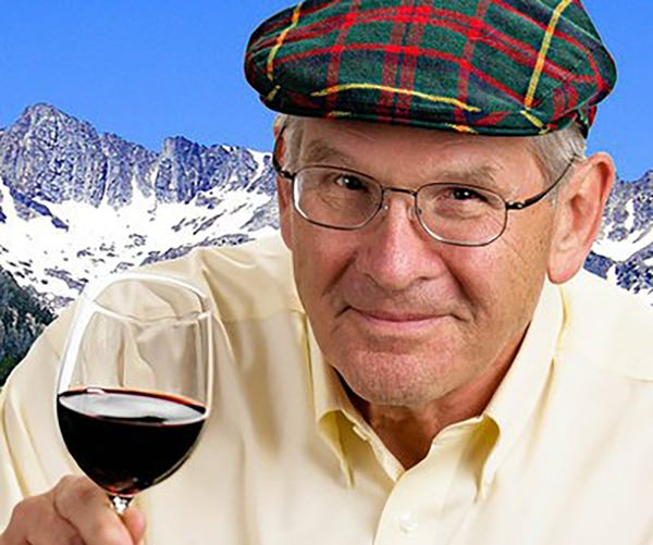 Rip McIntosh is seen wearing a plaid golf cap, glasses, and a yellow shirt. He's holding up a glass of red wine. Snow-covered mountains appear behind him in the background.