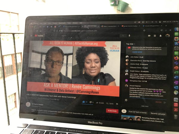 Photo of laptop running YouTube Live session with video of speaker and moderator and comments.