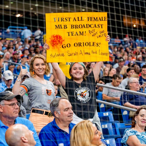 """Two fans at the game holding up a sign that says """"First all female MLB broadcast team! But not the last. Go Orioles!"""