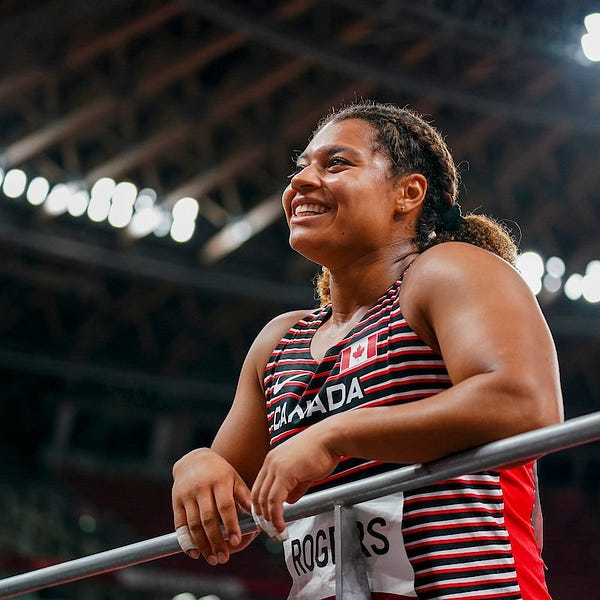 Camryn Rogers rests her hands on a railing and is smiling.