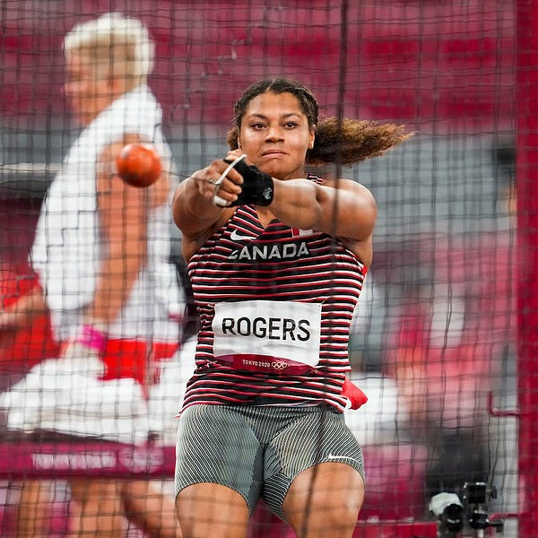 Camryn Rogers holding the hammer, up in the air. Her ponytail is up in the air to the side.