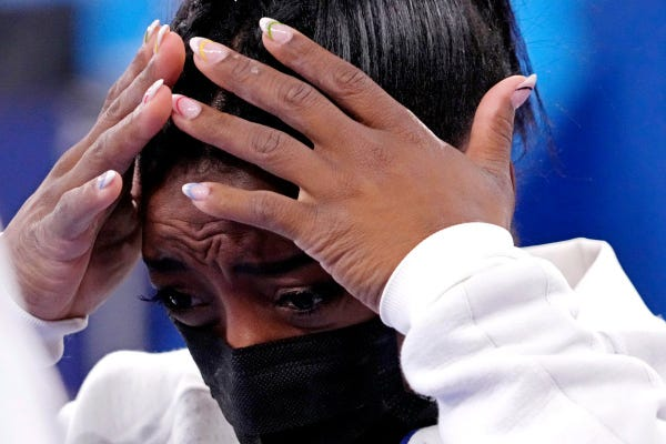 An upset Simone Biles is seen after withdrawing from the women's gymnastic team finals at the Tokyo Olympics.
