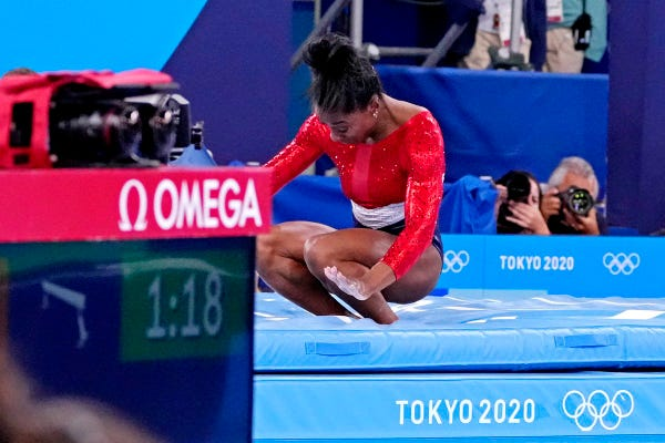 Simone Biles crouches on the mat after competing on the vault.