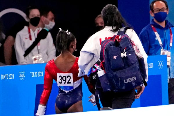 Simone Biles leaves the event with a coach.