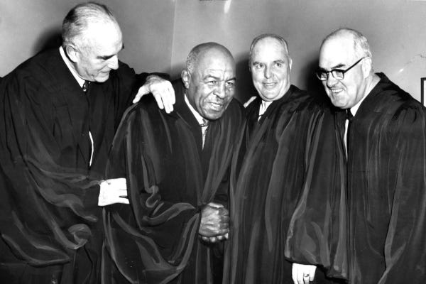 Duke Slater is surrounded by three colleagues, all of whom are wearing their black judicial robes.