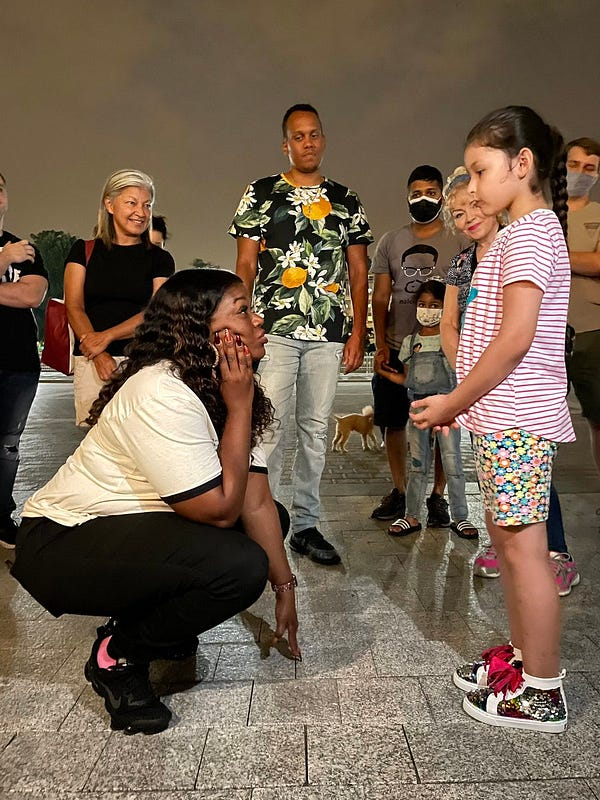 Congresswoman Cori Bush looks up at young girl as a small group of people behind them look on.