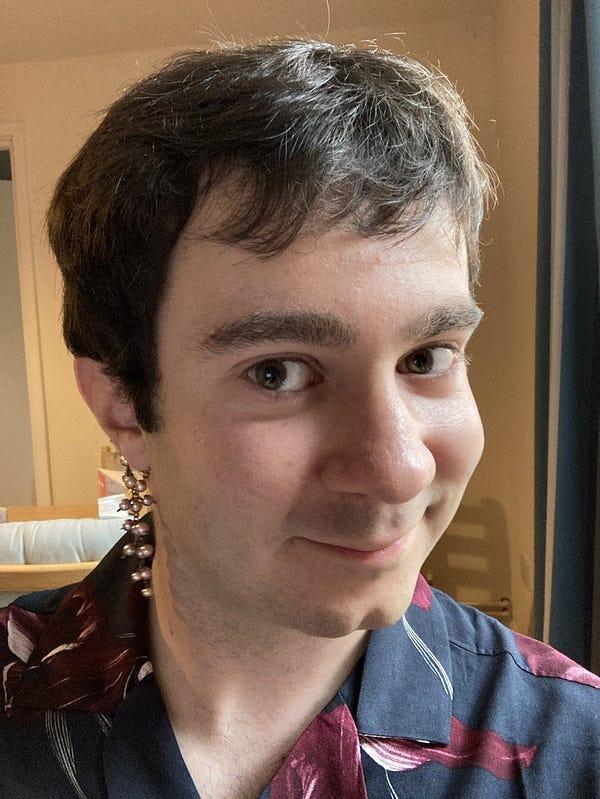 Picture of me smiling, wearing elegant earrings.